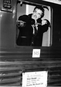 schwarz-weiß-Photographie eines Mannes, der aus einem Zug blickt