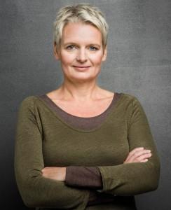 Portraitphotographie einer Frau mit kurzen blonden Haaren, braungrünem Pulli und verschränkten Armen
