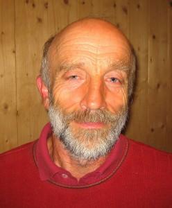 Portraitphoto: Mann mit weiß-grauem Vollbart und rotem Pullover
